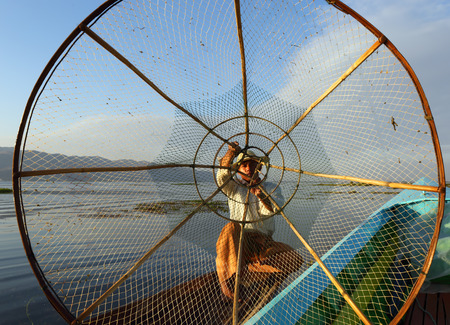 Myanmar travel attraction landmark - Traditional Burmese fisherman with fishing net at Inle lake in Myanmar Stock Photo
