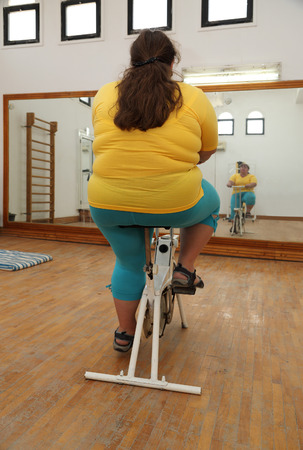 simulator: overweight woman exercising on bike simulator from behind