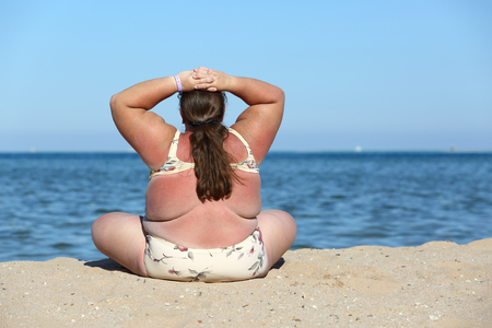 overweight woman sitting on sand beach, back shot
