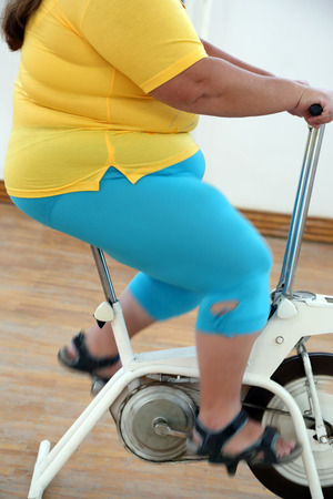 body of overweight woman exercising on bike simulator  photo