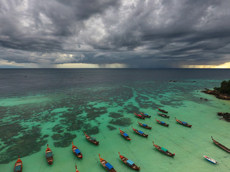 storm background: Long tail boats near tropical beach on the storm clouds background, Koh Lipe island, Thailand