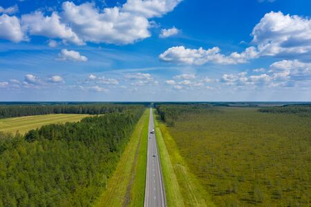Aerial top view landscape with a country road in the forest at summer Banco de Imagens