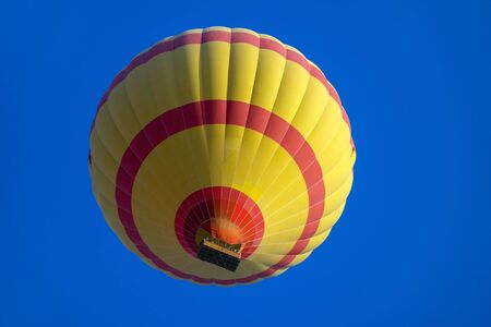 Yellow and red hot air baloon flying in blue sky