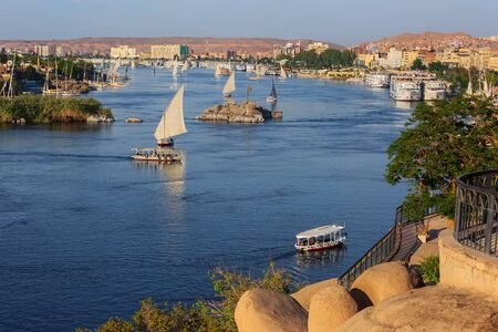 Beautiful landscape with felucca boats on Nile river in Aswan at sunset, Egypt Standard-Bild