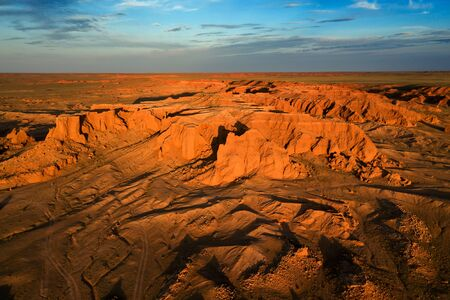 Aerial view of the Bayanzag flaming cliffs at sunset in Mongolia, found in the Gobi Desert