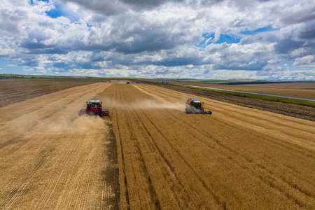 Aerial view of combine harvester working in golden wheat field
