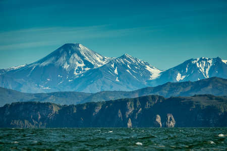 Beautiful summer landscape of Kamchatka - Three Brothers Rocks in Avacha Bay and cone of Volcano. Russian Far East