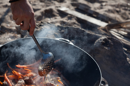 stewing: A man right arm is stewing meat with carrots in sunny day on a beach Stock Photo
