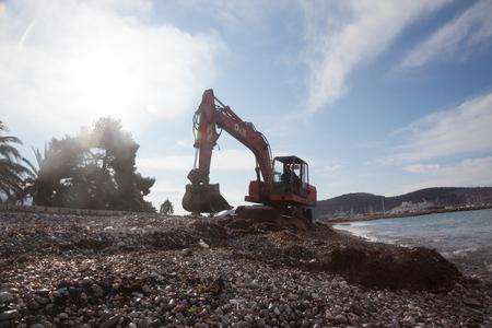 servicios publicos: servicios urbanos llevaron a cabo una limpieza de playas p�blicas antes del inicio de la temporada tur�stica con la ayuda de rojo excavadora Editorial