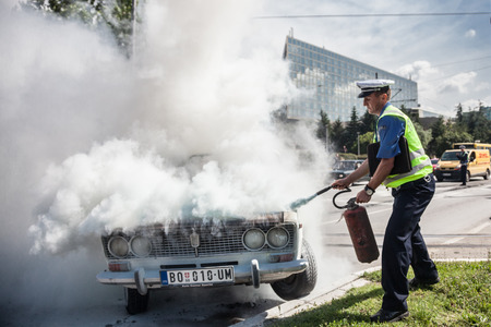 ignition: The policeman douses a fire after car ignition accident  at one of crossroads of Belgrad. Serbia Editorial