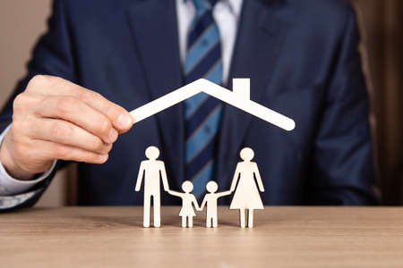 Concept of family insurance with hands protecting a family. A roof over the family Standard-Bild