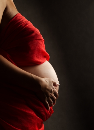 expectant mother holding her belly and wearing red fabric on black background photo