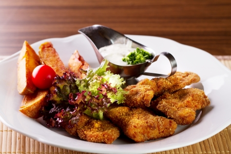 grilled potato: Wiener Schnitzel with grilled potato and dressing on white plate