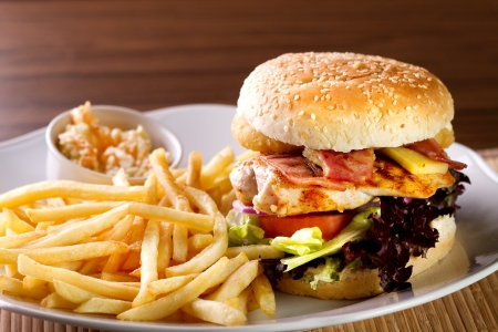 french roll: delicious hamburger with fries and salad on white plate