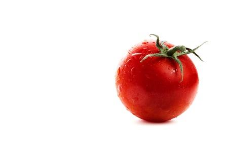 Wet tomato on white background photo