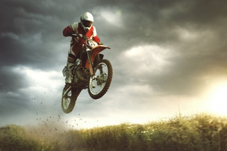 A picture of a biker making a stunt and jumps in the air photo