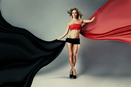 Beautiful woman posing in red and black waving fabric against grey background photo