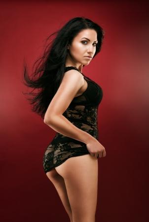 mujer desnuda de espalda: Foto de estudio de mujer sexy en ropa interior negro sobre fondo rojo