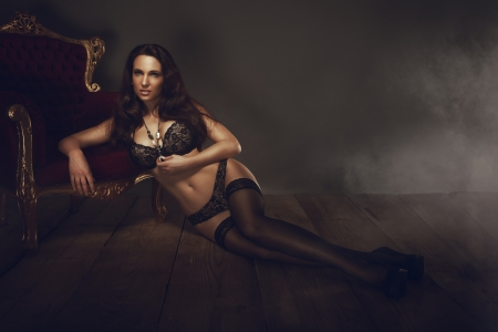 Sexy brunette woman lying on wooden floor photo