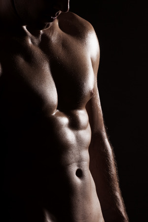 nipple man: Strong athletic man torso isolated on black background