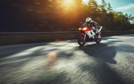 casco de moto: hombre montado en motocicleta en la carretera de asfalto Foto de archivo