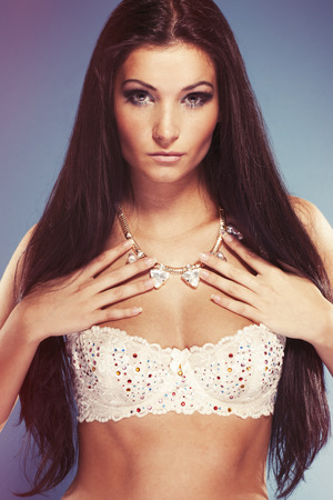 sexy bra: Portrait of a young beuatiful girl holding her jewellery and wearing sexy bra