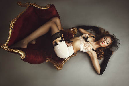 Young beautiful woman lying on chair - retro style 스톡 콘텐츠