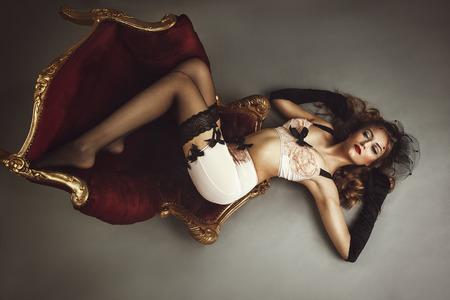 fetysz: Młoda piękna kobieta, leżąc na krześle - stylu retro