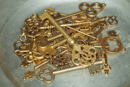 Group of antique golden door keys on iron plate