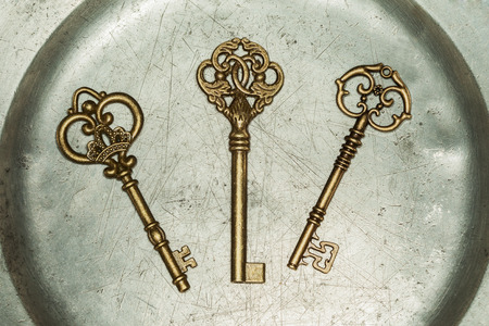 Three antique golden door keys on iron plate Stock fotó
