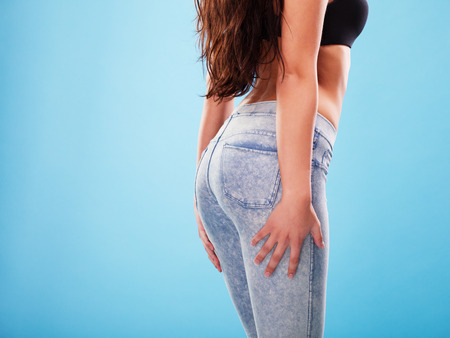 Sexy woman buttocks in jeans on the blue background