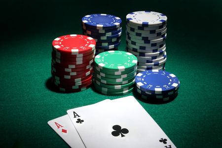 Two aces and stack of Casino Chips in background photo