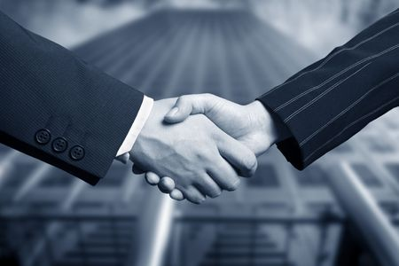 pact: business hand shake and a office in background