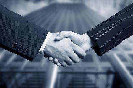 pacto: negocios agitar la mano y una oficina en el fondo  Foto de archivo