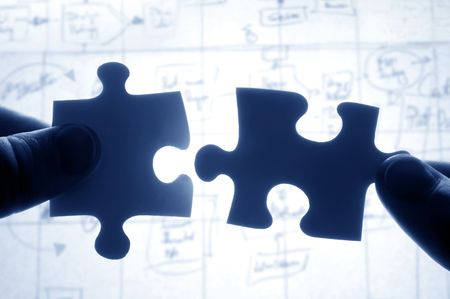 Hands trying to fit two puzzle pieces together photo