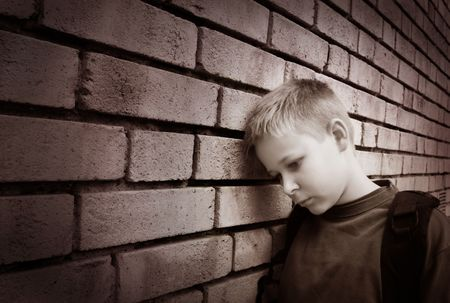 Black and white picture of an upset boy leaning against a wall photo