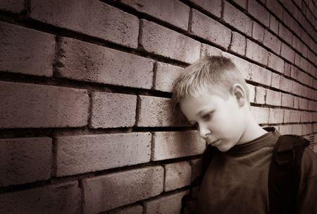 chłopięctwo: Czarno-biały obraz z zaburzyłyby chłopiec pochylony przed ścianą