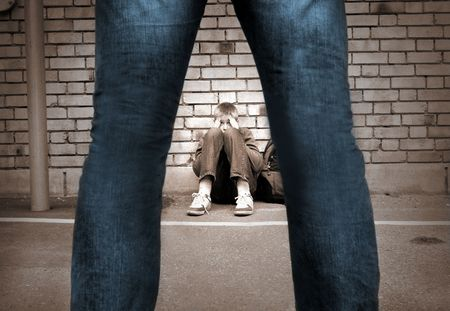 tormented: frightened boy at the school yard and a mans legs Stock Photo