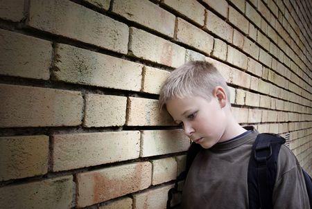 lesionado: molesto muchacho inclinado contra una pared