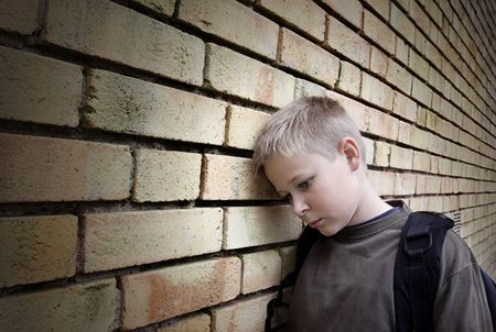 injured: upset boy leaning against a wall Stock Photo