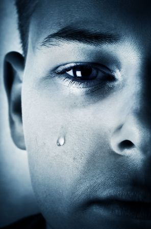 man crying: Sad face close-up - a tear is running down a cheek