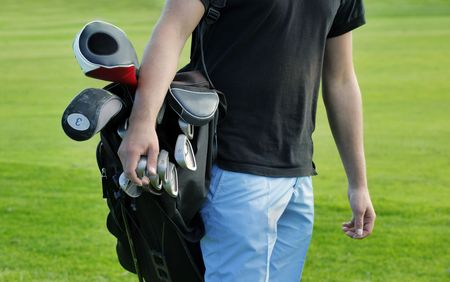 Male golfer carrying clubs, close-up Stock Photo - 5497913