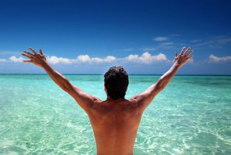 Man standing looking at ocean with arms stretched out Stock Photo - 6924859