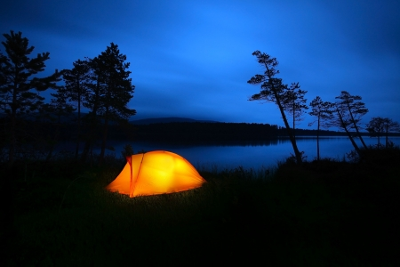 camping equipment: A tent lit up at dusk
