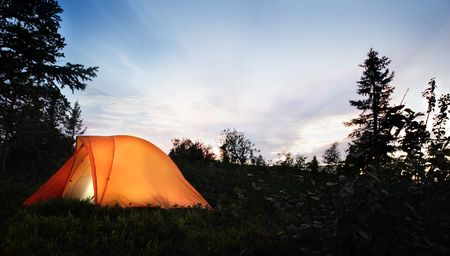 camping: A tent lit up at dusk