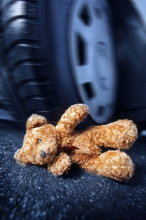 Teddy bear in front of a car