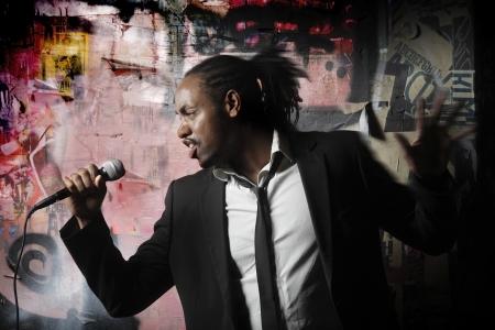 rapero: hombre posando con un micr�fono de pared de graffiti Foto de archivo