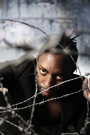 Portrait of a man holding barbed wire and a graffiti wall in background Stock Photo - 9785412