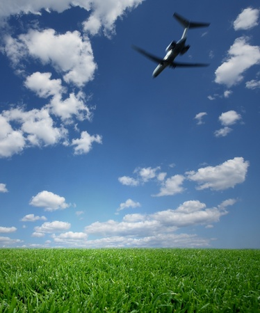 Airplane Flying in a Blue Sky over Green Grass Stock Photo