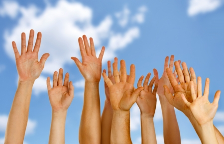 Hands raised up in air across blue sky  photo